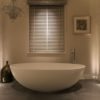 a free standing bath is lit with both up and downlights
