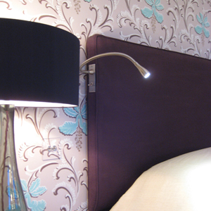 a dedicated bedside reading light by a velvet bedhead