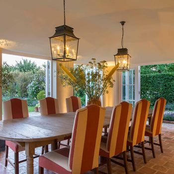 traditional conservatory dining room with lanterns and uplights