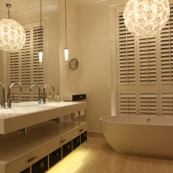 contemporary bathroom with floating basin and back lit bath with large decorative pendant