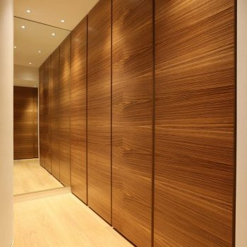 flush wooden cupboards in dressing room with downlights