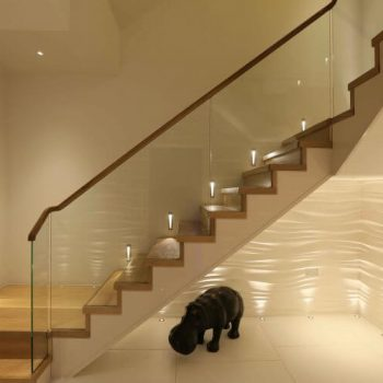 Glass ballustrade with floor washers and uplights to a textured wall