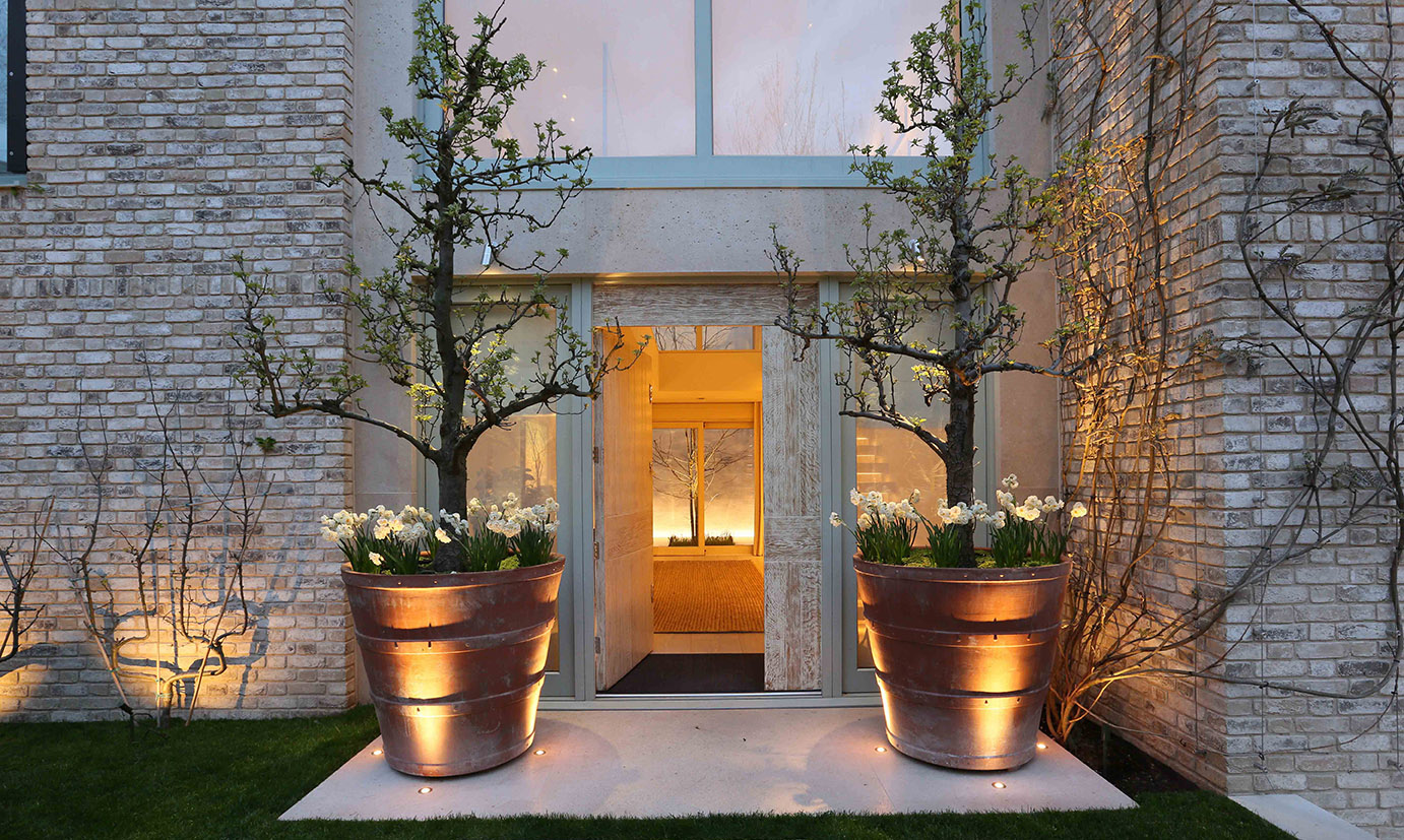 entrance lighting with over-scaled pots and courtyard beyond