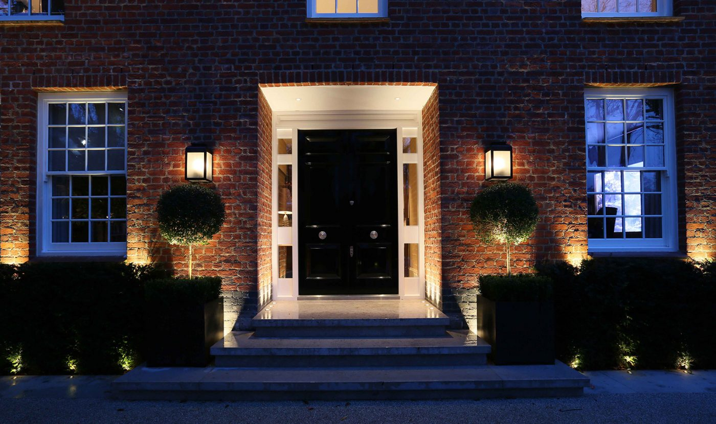 view to front door with facade and front door lighting