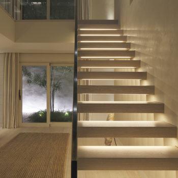 Contemporary hall with linear lighting under each stair tread