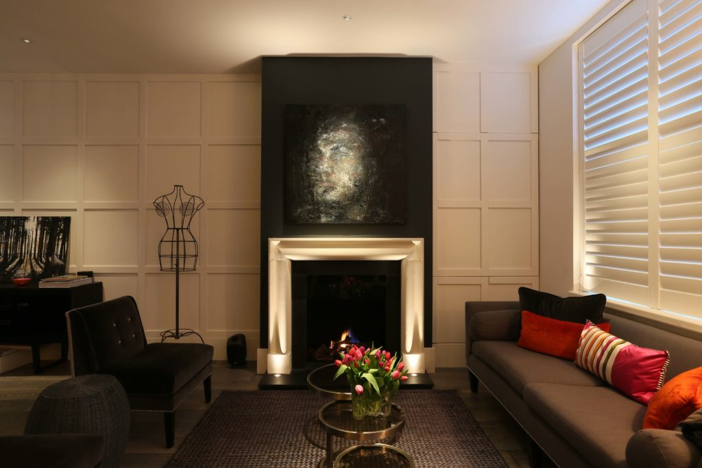 contemporary living room with uplit fireplace and art