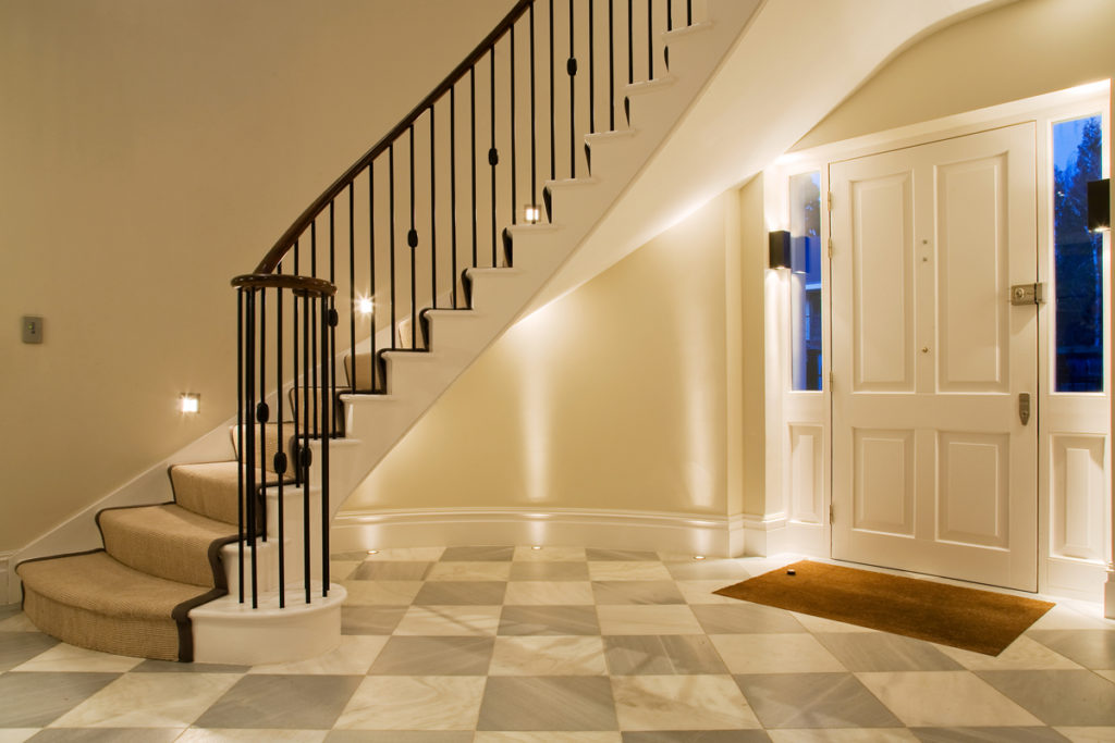 sweeping staircase with lighting underneath in hall