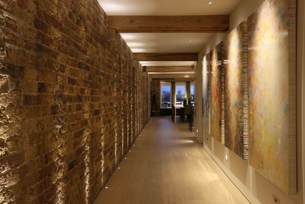 long corridor with up and downlights lit by lighting designer