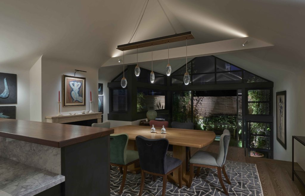 subtle lighting of view across dining room to garden beyond