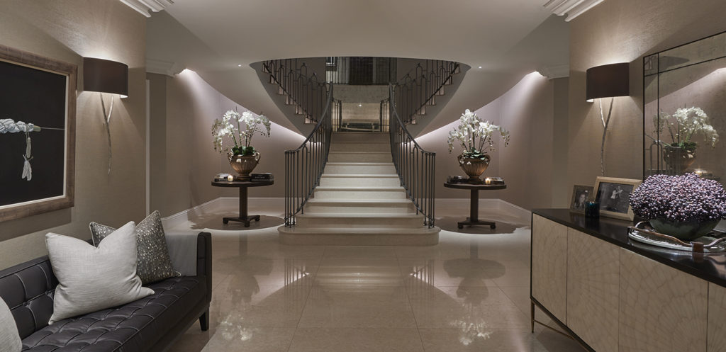 dramatic sweeping staircase underlit with artificial light