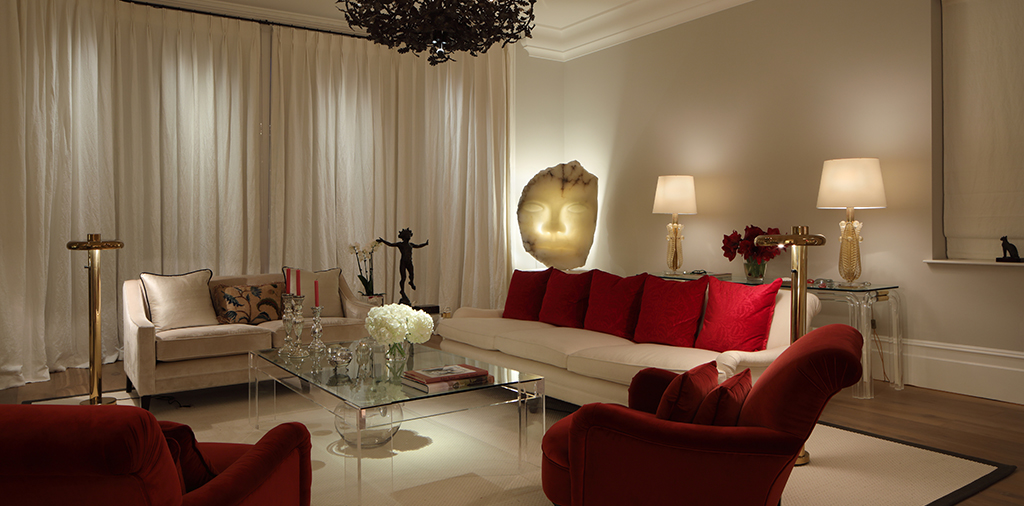 well lit drawing rom with white sofas and red cushions