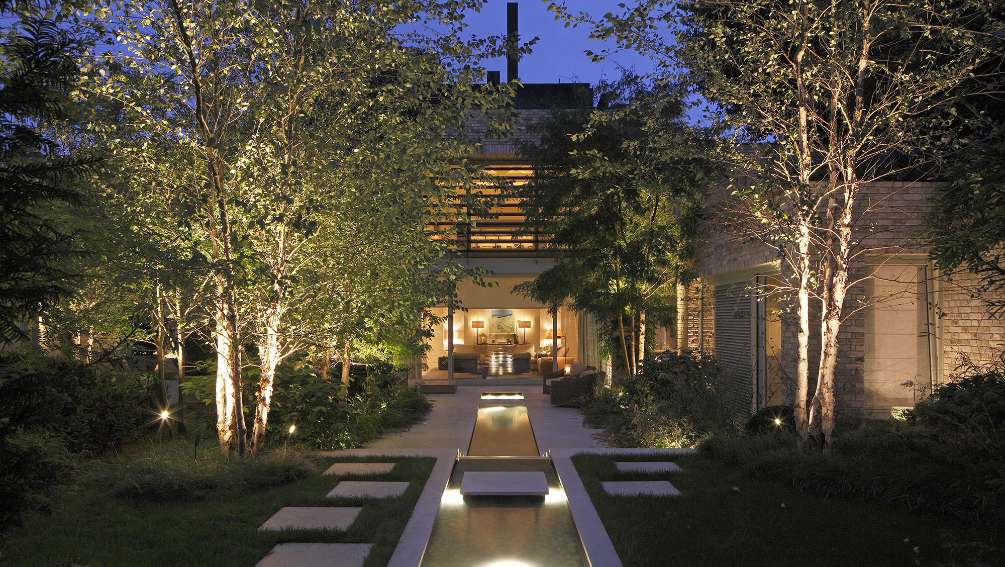 Large garden with view to house beautifully lit