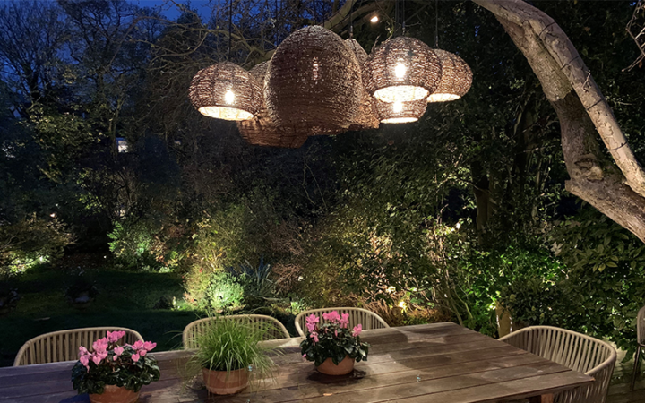 A tree provides support to several basket lanterns that give soft light to the dining table in a relaxed natural fashion.