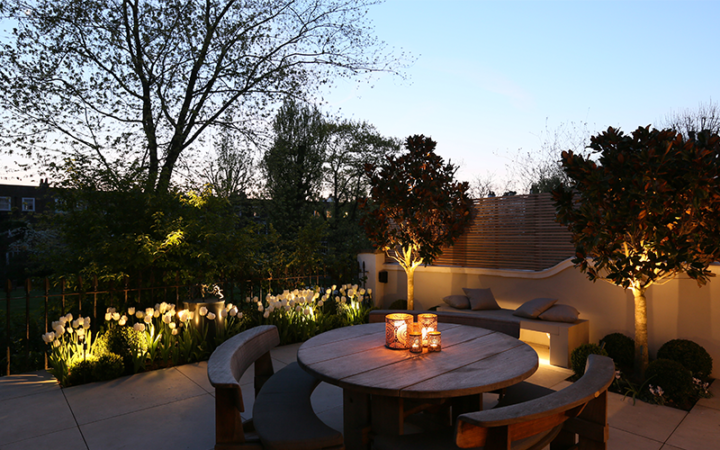 1 watt floodlights to the front of the tulips and two 1 watt spotlights to the small trees, plus a linear LED below the bench and candles on the table all create the mood in this outdoor dining area.