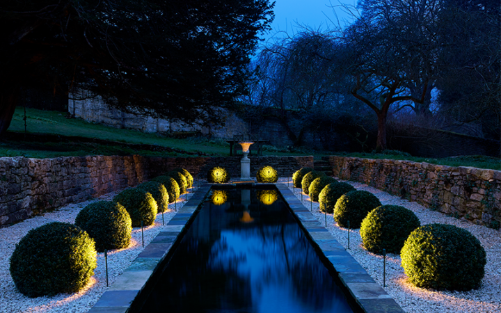 water feature lit with spike lights either side
